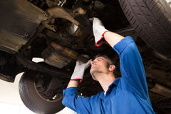 Mechanic examining under the car Stock Images