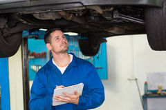Mechanic examining under the car Stock Photos
