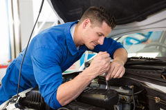 Mechanic examining under hood of car Stock Photo