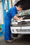 Mechanic examining under hood of car Royalty Free Stock Image