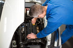 Mechanic examining under hood of car Stock Images