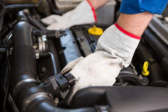 Mechanic examining under hood of car Royalty Free Stock Photo
