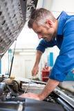 Mechanic examining under hood of car Stock Images