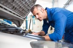 Mechanic examining under hood of car Stock Photos