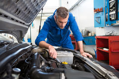 Mechanic examining under hood of car Stock Photos