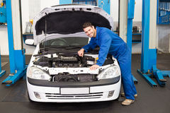 Mechanic examining under hood of car Royalty Free Stock Photography
