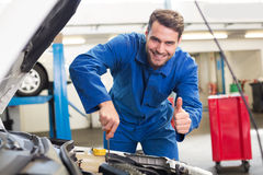 Mechanic examining under hood of car. At the repair garage Stock Photography