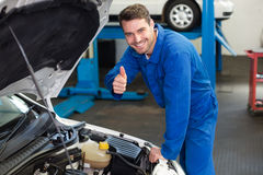 Mechanic examining under hood of car Royalty Free Stock Images