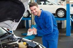 Mechanic examining under hood of car Royalty Free Stock Photos