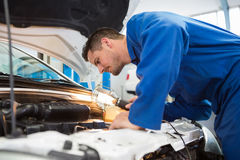 Mechanic examining under hood of car with torch Stock Images