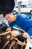 Mechanic examining under hood of car with torch Stock Photos