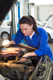 Mechanic examining under hood of car with torch Stock Image