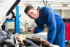 Mechanic examining under hood of car with torch Stock Photo