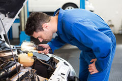 Mechanic examining under hood of car with torch Royalty Free Stock Photo