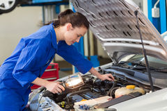 Mechanic examining under hood of car with torch. At the repair garage stock photos