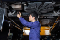 Mechanic Examining Underneath Lifted Car. Side view of male mechanic examining underneath lifted car at auto repair shop Royalty Free Stock Photo