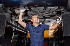 Mechanic Examining Underneath Lifted Car royalty free stock photography