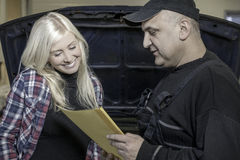 Mechanic explaining repair. Mechanic holding yellow folder explaining repair to costumer in realistic settings stock photo