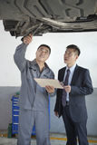 Mechanic Explaining to Businessman Royalty Free Stock Photography