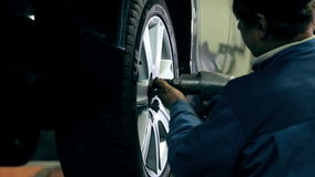 Mechanic fasten the wheel on the car stock video footage