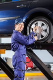 Mechanic Filling Air Into Car Tire At Garage Stock Photos
