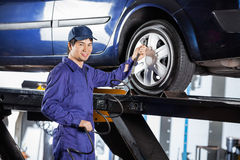 Mechanic Filling Air Into Car Tire At Garage Royalty Free Stock Photography