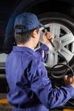Mechanic Filling Car Tire At Garage Royalty Free Stock Photo