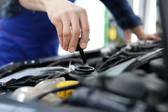 The mechanic fills the tank power steering fluid. Car mechanic exchanges steering system fluid stock photos