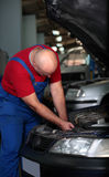 A mechanic fix a car. A mechanic hard working on a car in a motor repair shop with face down stock photo