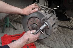 Car mechanic work on disc brakes Stock Images