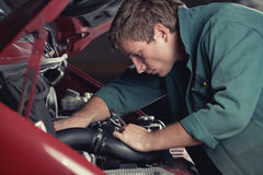 Mechanic fixing auto in car service. Mechanic at work fixing car in auto service Royalty Free Stock Images