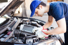 Mechanic fixing a car engine. Mechanic working on a car engine stock photography