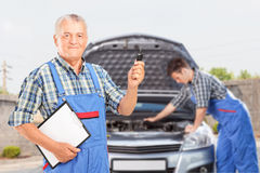 Mechanic fixing a car problem. Mature mechanic in uniform holding a car key and another mechanic performing a car check in the background Royalty Free Stock Photo