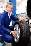 Mechanic fixing a car puncture Royalty Free Stock Images