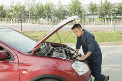 Mechanic Fixing Car by Roadside Royalty Free Stock Images
