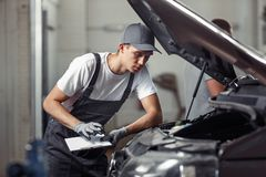A mechanic is fixing a car at a car service royalty free stock photo