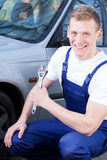 Mechanic fixing car and smiling Royalty Free Stock Photos