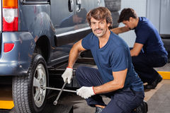 Mechanic Fixing Car Tire At Auto Repair Shop Royalty Free Stock Photography