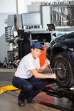 Mechanic Fixing Car Tire At Garage Stock Images