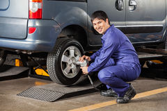 Mechanic Fixing Car Tire Pneumatic Wrench At Garage Royalty Free Stock Photography