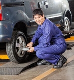 Mechanic Fixing Car Tire With Pneumatic Wrench. Portrait of happy mechanic fixing car tire with pneumatic wrench at garage stock photography