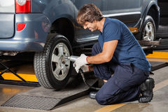 Mechanic Fixing Car Tire At Repair Shop. Male mechanic holding pneumatic wrench while fixing car tire at auto repair shop stock image
