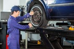 Mechanic Fixing Car Tire At Repair Shop Stock Images