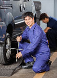 Mechanic Fixing Car Tire With Rim Wrench At Royalty Free Stock Photography