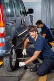Mechanic Fixing Car Tire With Rim Wrench At Workshop Stock Photography