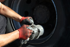 Mechanic fixing car wheel Stock Photos