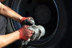 Mechanic fixing car wheel Stock Photos
