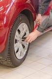 Mechanic fixing car wheel. Stock Images