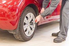 Mechanic fixing car wheel. Stock Image