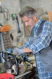 Mechanic fixing a chainsaw. Outdoor stock photo